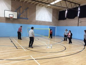5 people playing badminton in a sports hall